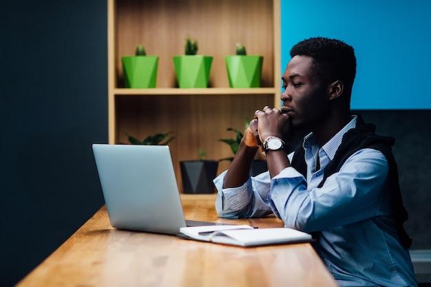 Concepto de autónomo. hombre en ropa casual está examinando documentos mientras trabaja con una computadora portátil en la cocina. trabajando en casa.