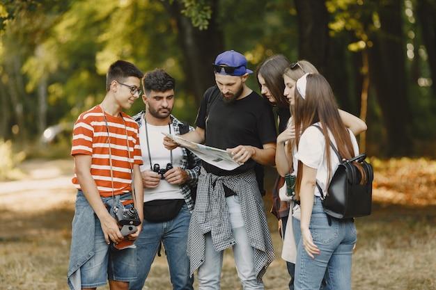 Concepto de aventura, caminata y personas. grupo de amigos sonrientes en un bosque. hombre con mapa.