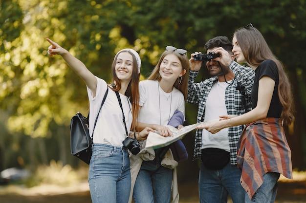 Concepto de aventura, viajes, turismo, caminata y personas. grupo de amigos sonrientes en un bosque. hombre con binocularus.