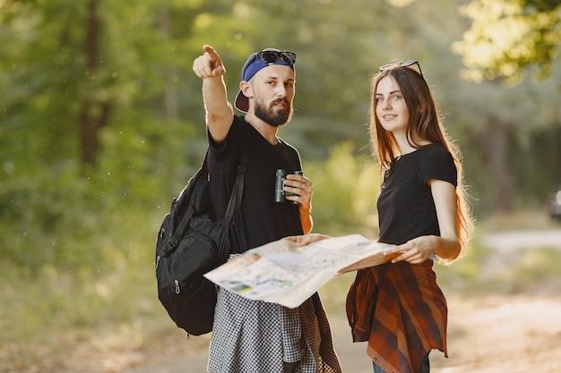 Concepto de aventura, viajes, turismo, caminata y personas. pareja en un bosque.