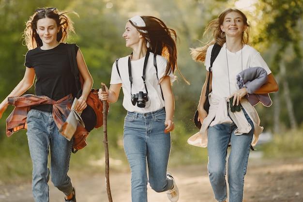 Concepto de aventura, viajes, turismo, caminata y personas. tres chicas en un bosque.