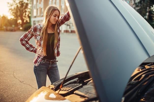 Concepto de avería de coche, mujer contra el capó abierto