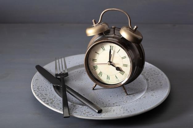 Concepto de ayuno intermitente, dieta cetogénica, pérdida de peso. despertador tenedor y cuchillo en un plato