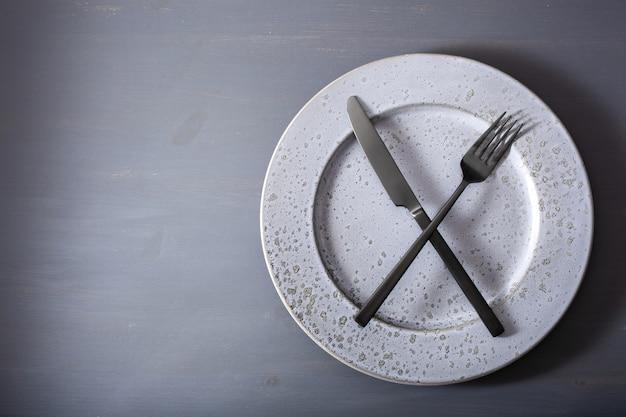 Concepto de ayuno intermitente y dieta cetogénica, pérdida de peso. tenedor y cuchillo cruzado en un plato