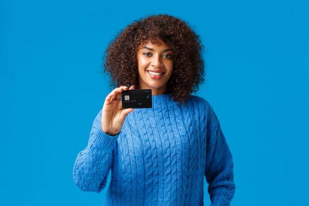 Concepto de banca, compras y finanzas. atractiva mujer afroamericana agradable con cabello afro, suéter de invierno, mostrando tarjeta de crédito, pagando compra en línea, prepararse para las vacaciones
