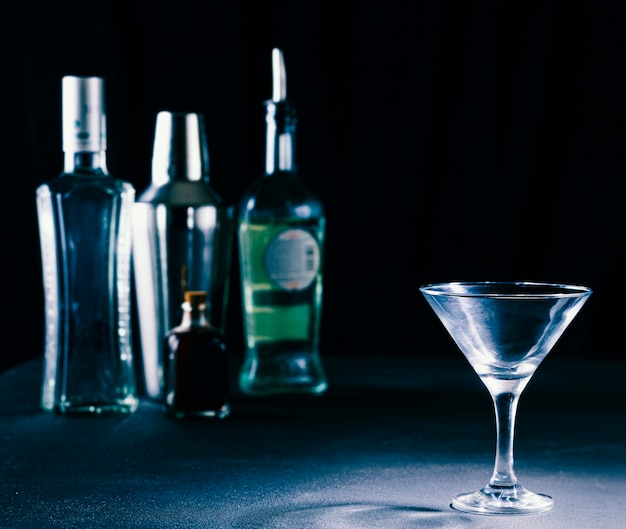 Concepto de barra. alcohol embotellado, coctelera y copa de cóctel. copie el espacio.