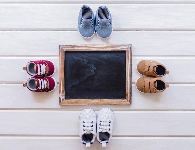 Concepto de bebé con cuatro pares de zapatos y pizarra