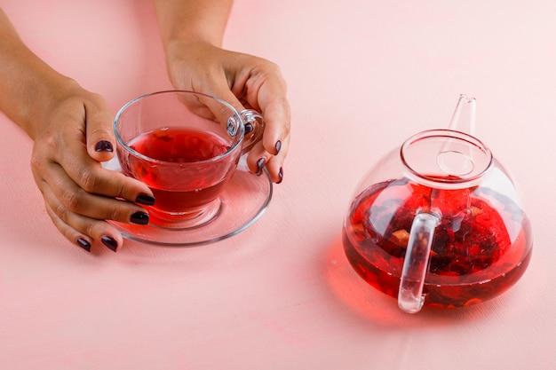 Concepto de bebida caliente con tetera en mesa rosa mujer sosteniendo la taza de té de cristal.