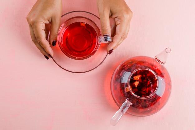Concepto de bebida caliente con tetera en mesa rosa plana lay. mujer sosteniendo una taza de té de cristal.