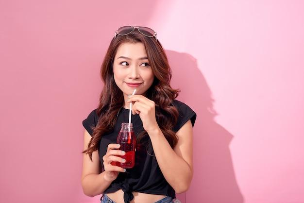 Concepto de bebidas, personas y estilo de vida - cerca de mujer feliz bebiendo cola con pajita en casa