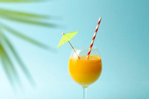Concepto de bebidas de verano. zumo de naranja en una taza de cristal sobre un fondo azul de color. fondo mínimo de verano tropical