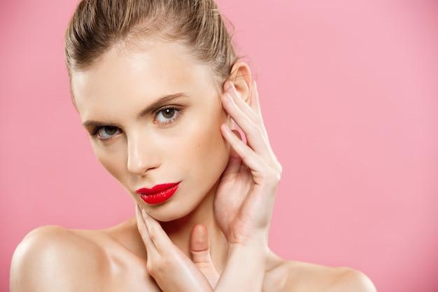 Concepto de belleza - close up hermosa mujer morena joven cara retrato. modelo de belleza chica con cejas brillantes, maquillaje perfecto, labios rojos, tocando su cara. aislado sobre fondo de color rosa