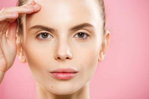 Concepto de belleza - close up retrato de niña caucásica atractiva con la piel de belleza natural aislado en fondo de color rosa con copia espacio.