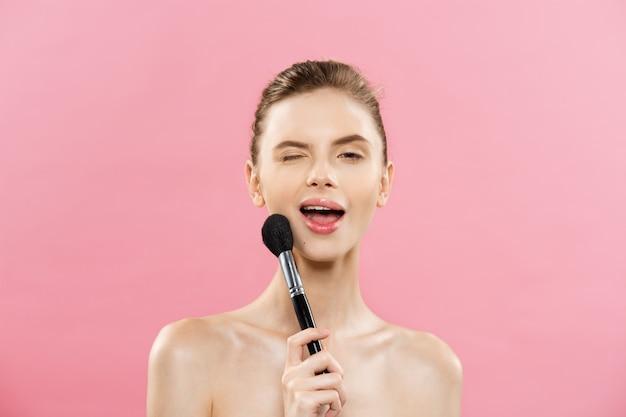 Concepto de belleza - closeup hermosa mujer caucásica aplicar maquillaje con cepillo de polvo de cosméticos. piel perfecta. aislado en fondo rosado y espacio de la copia.