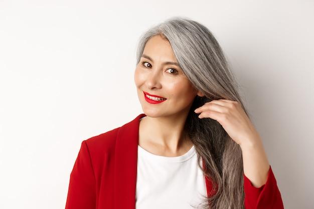 Concepto de belleza y cuidado del cabello. cerca de elegante mujer senior asiática mostrando cabello gris brillante y saludable, sonriendo y mirando a un lado, fondo blanco.