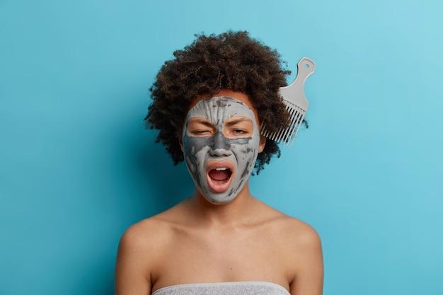 Concepto de belleza para el cuidado del cuerpo. hermosa mujer de piel oscura aplica mascarilla facial tiene peine atascado en bostezos de cabello rizado