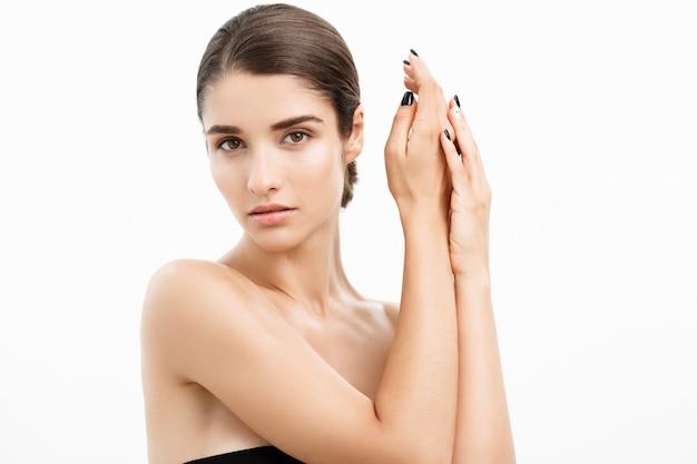 Concepto de belleza y cuidado de la piel. cerrar joven tocando su piel sobre fondo blanco.
