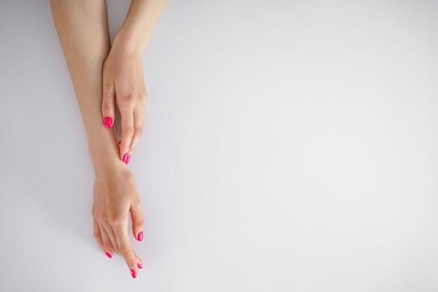 Concepto de belleza y cuidado de la piel con espacio para texto. hermosas manos femeninas y hermosa manicura sobre un fondo blanco, plano laical.