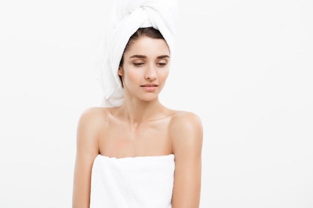 Concepto de belleza y cuidado de la piel - mujer joven caucásica con toalla de baño en la cabeza cubriendo sus pechos, en blanco.