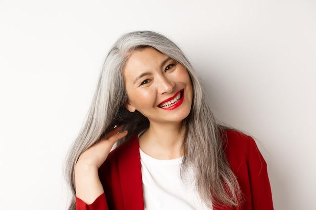 Concepto de belleza y envejecimiento. cerca de la mujer mayor asiática con labios rojos, cabello gris largo sano, sonriendo a la cámara, de pie sobre fondo blanco.