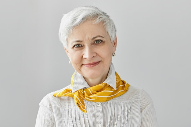 Concepto de belleza, estilo, moda y envejecimiento. encantadora elegante mujer jubilada de pelo gris vistiendo elegante pañuelo de seda amarillo sonriendo felizmente, disfrutando de su edad madura, sin tener miedo de envejecer
