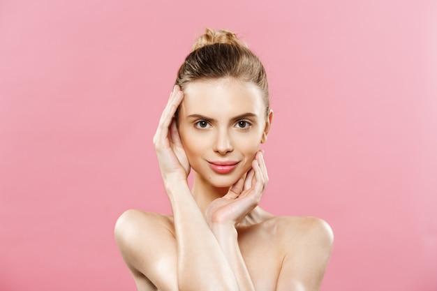 Concepto de belleza - hermosa mujer con piel fresca limpia de cerca en el estudio de color rosa. cara del cuidado de la piel. cosmetología.
