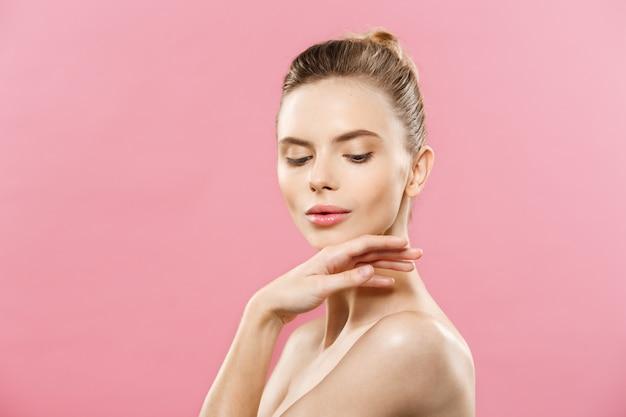 Concepto de belleza - hermosa mujer de raza caucásica con piel limpia, maquillaje natural aislado en fondo de color rosa brillante con copia espacio.
