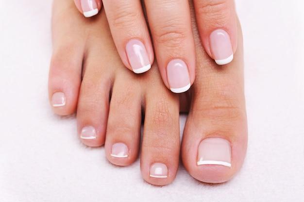 Concepto de uñas de belleza de una mano y pies femeninos con hermosa manicura y pedicura francesa