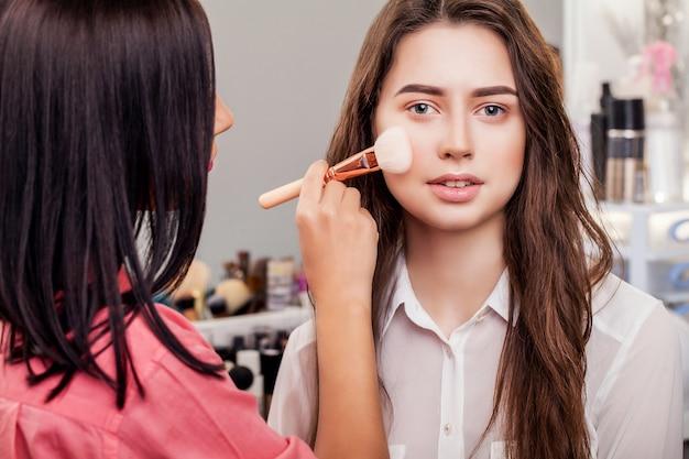 Concepto de belleza, maquillaje, cosméticos y personas - cerca de la cara sonriente de la mujer joven aplicando rubor con pincel de maquillaje