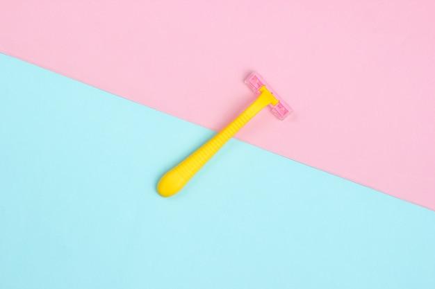 Concepto de belleza minimalista. navaja de plástico amarillo sobre azul rosa pastel. vista superior