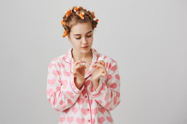 Concepto de belleza y moda. chica en rizadores de pelo y pijama aplicando esmalte de uñas