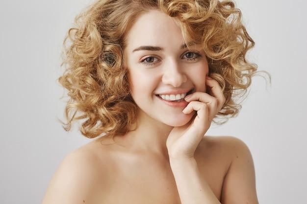Concepto de belleza y moda. despreocupada hermosa chica con cabello rizado y hombros desnudos sonriendo