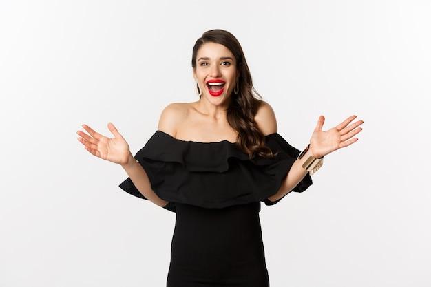 Concepto de belleza y moda. imagen de mujer joven sorprendida y feliz en traje de fiesta reaccionando a las buenas noticias, levantando las manos y sonriendo asombrado, fondo blanco.
