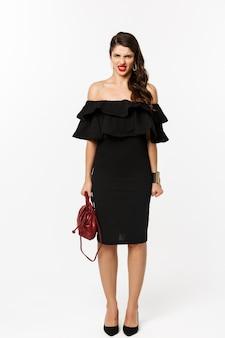Concepto de belleza y moda. longitud total de mujer enojada en vestido de fiesta negro y tacones altos, expresar desdén y hacer muecas a la cámara, enojado con la persona, fondo blanco.