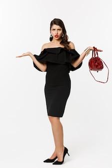 Concepto de belleza y moda. longitud total de mujer de glamour decepcionada que parece confundida, levantando las manos y mirando perpleja, con vestido de fiesta y tacones altos.