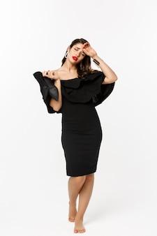 Concepto de belleza y moda. longitud total de mujer joven cansada en elegante vestido negro, quitándose los tacones altos y mirando exhausto, de pie sobre fondo blanco.