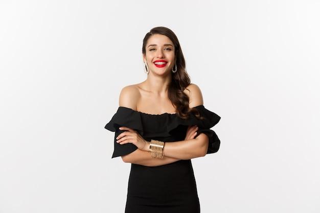 Concepto de belleza y moda. modelo de mujer atractiva en vestido de fiesta y lápiz labial rojo, sonriendo complacido, mirando feliz, de pie sobre fondo blanco.