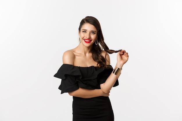 Concepto de belleza y moda. mujer coqueta en vestido negro, labios rojos, jugando con el pelo y escuchando, mirando a la cámara con interés, de pie sobre fondo blanco.