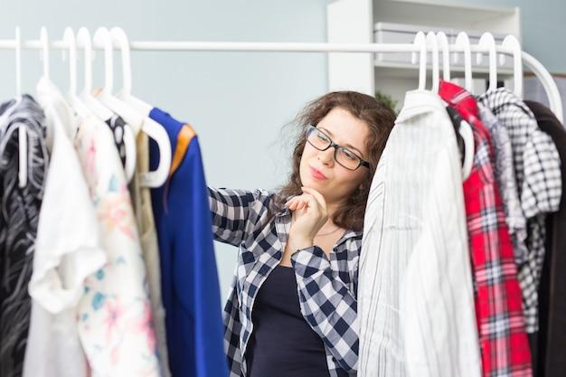 Concepto de belleza, moda y personas: hermosa mujer seria con gafas negras elige vestidos