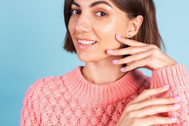 Concepto de belleza, mujer bonita con manicura de color de uñas rosa brillante en la pared