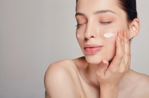 Concepto de belleza mujer hermosa joven con los ojos cerrados está aplicando crema cosmética en su rostro. cuidados en el hogar. protección de la piel. piel seca.