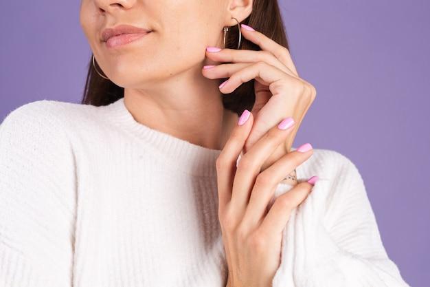 Concepto de uñas de belleza, mujer mezquina con manicura de color rosa primavera suéter blanco pared púrpura