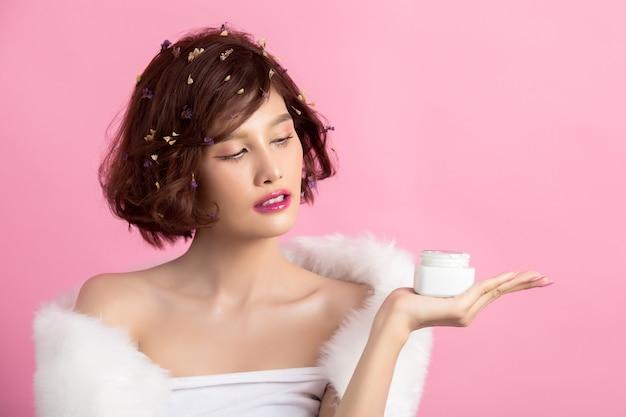 Concepto de belleza mujer tiene una crema hidratante en la mano