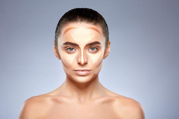 Concepto de belleza. retrato de mujer hermosa con contorno en la cara. tipos de maquillaje de dibujo, cabeza y hombros de niña con maquillaje desnudo mirando a la cámara