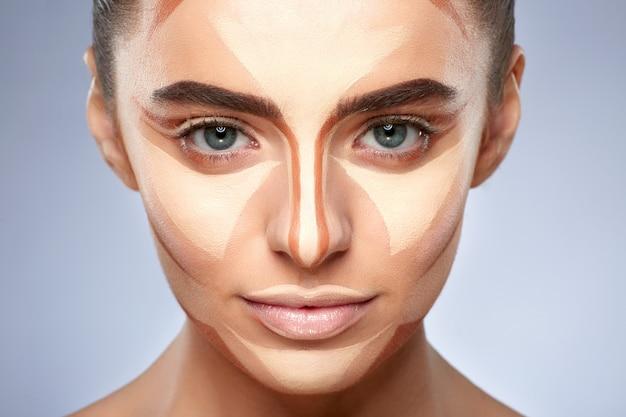 Concepto de belleza. retrato de mujer hermosa con contorno en la cara. tipos de maquillaje de dibujo, primer plano de chica con maquillaje desnudo mirando a la cámara