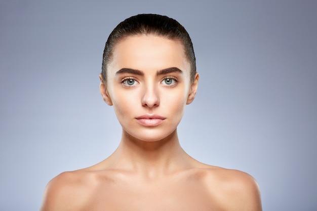 Concepto de belleza. retrato de mujer hermosa sin maquillaje. cabeza y hombros de niña con maquillaje nude mirando a cámara