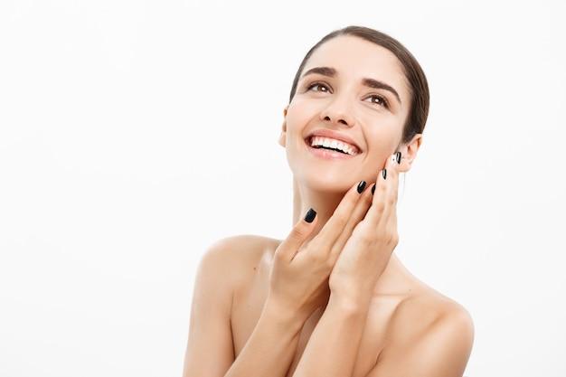 Concepto de belleza y spa. encantadora mujer joven con una piel clara perfecta sobre fondo blanco.