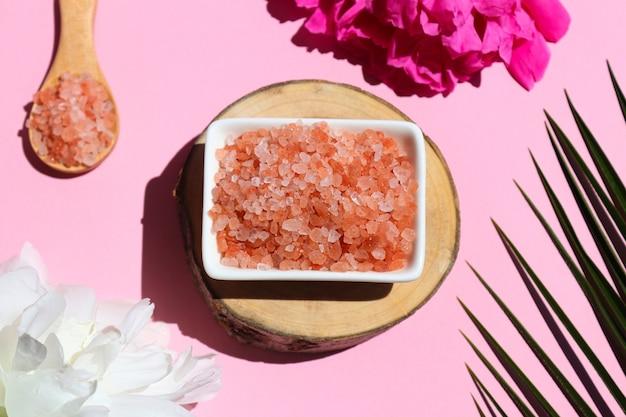 Concepto de belleza y spa sal del himalaya rosa en un corte de madera con hojas de palmera y flores de peonía