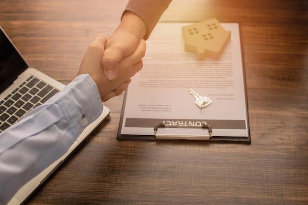 El concepto de bienes raíces, la agencia bancaria se da la mano con el cliente o el comprador de la casa después de una comunicación exitosa y firma el contrato