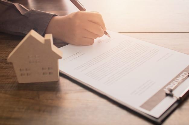 Concepto de bienes raíces, cliente o signo de comprador de casa en papel de contrato